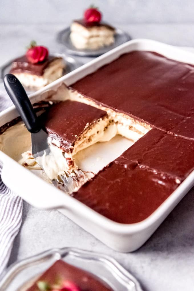 An image of a sliced eclair cake with a spatula for serving.