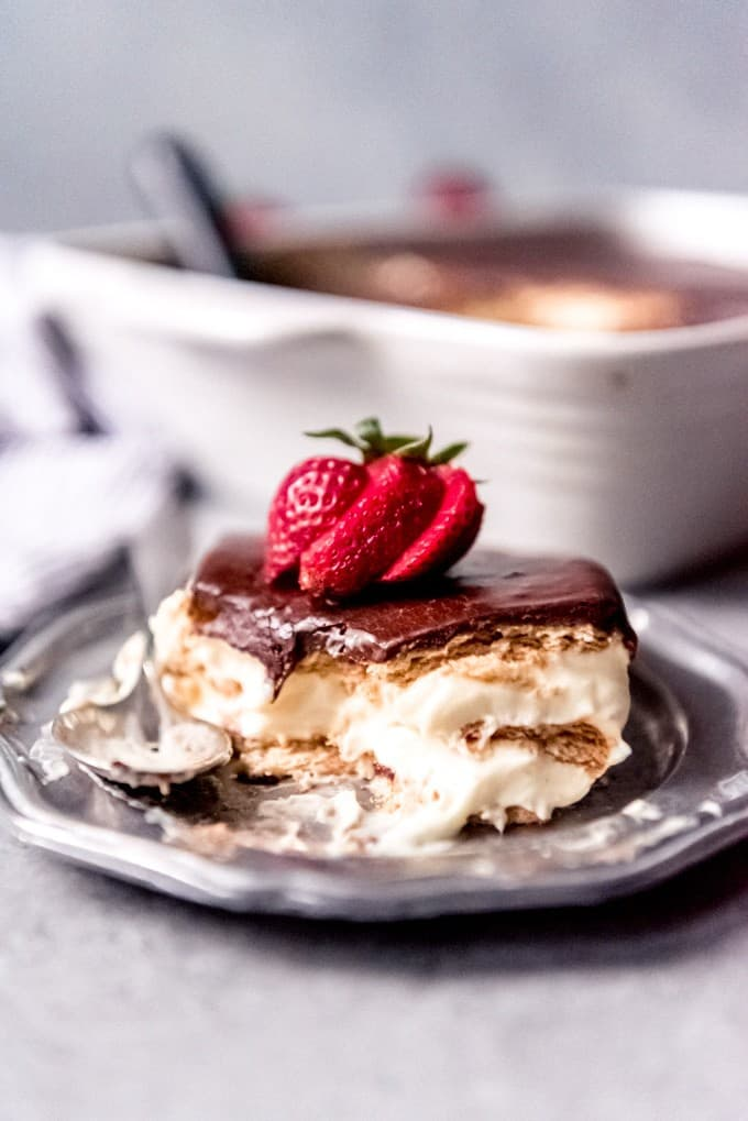 An image of a piece of no-bake chocolate eclair cake with a sliced strawberry on top.