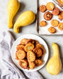 a stack of fried yellow squash on a plate with more squash whole and fried around it