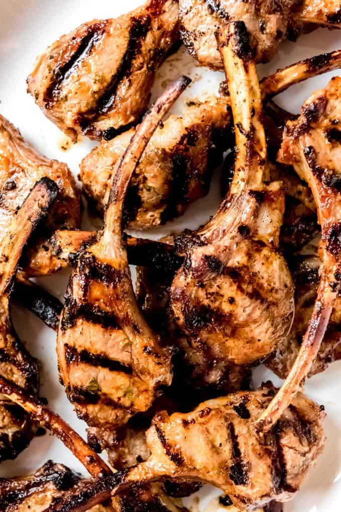 A close-up image of grilled lamb chops with a spicy sweet sriracha, honey, mustard, mayo, and mint marinade.