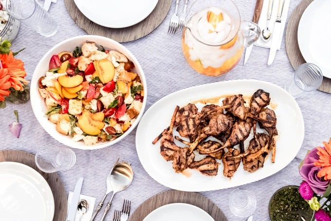 An image of an outdoor tablescape with peach panzanella salad and grilled lamb chops.
