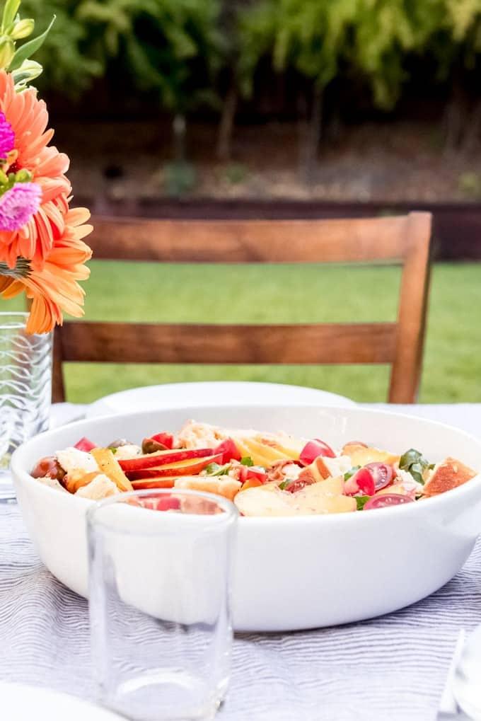 An image of a large bowl of peach panzanella salad.