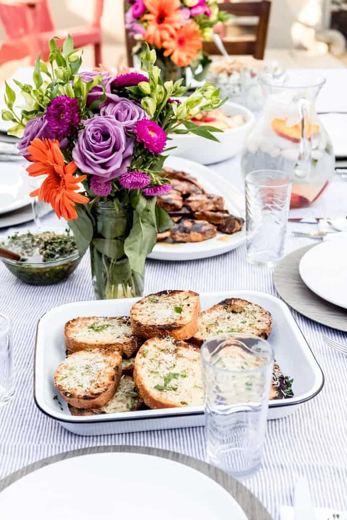 An image of a flower arrangement and plate of grilled garlic bread on a table set outside for al fresco dining.