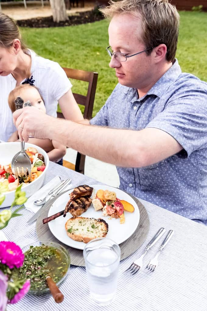 An image of a man serving himself salad to go with grilled lamb chops and garlic bread.