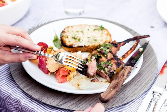 An image of a bite of marinated grilled lamb chop on a fork.
