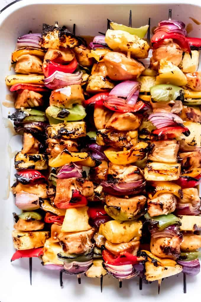 An image of grilled pineapple, teriyaki chicken, red onions, and colorful peppers on wooden skewers.