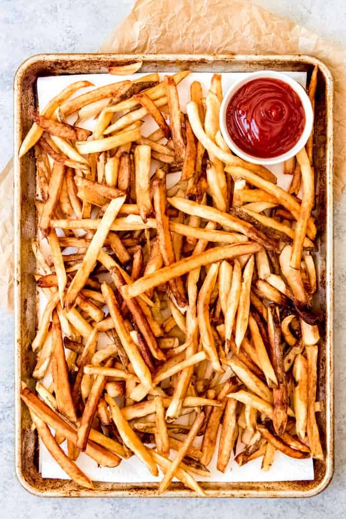 An image of a large baking sheet piled with crispy, golden brown french fries.