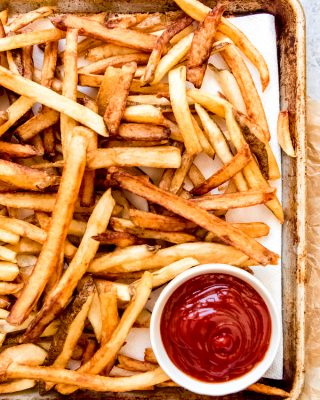 An image of double-fried french fries with ketchup.