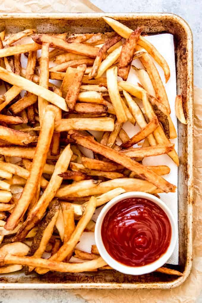 An image of golden brown homemade french fries on a baking sheet with a bowl of ketchup for dipping.