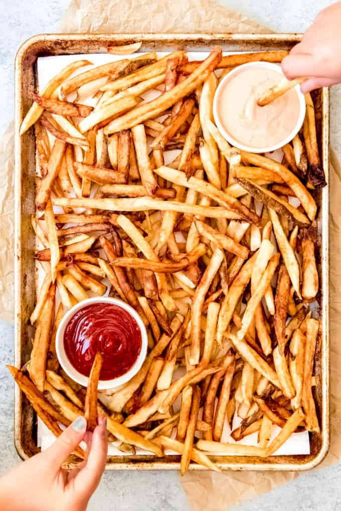 An image of hands dipping homemade french fries into ketchup and fry sauce.