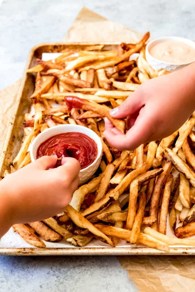 An image of hands dipping homemade french fries into a bowl of ketchup.