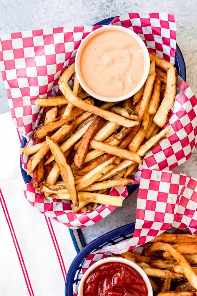 An image of a basket filled with french fries and a bowl of fry sauce.