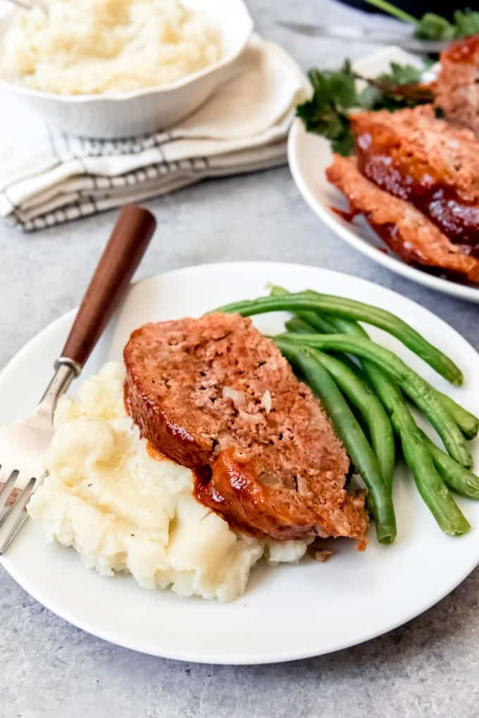 An image of a plate with a thick slice of Instant Pot meatloaf, creamy mashed potatoes, and green beans on it.