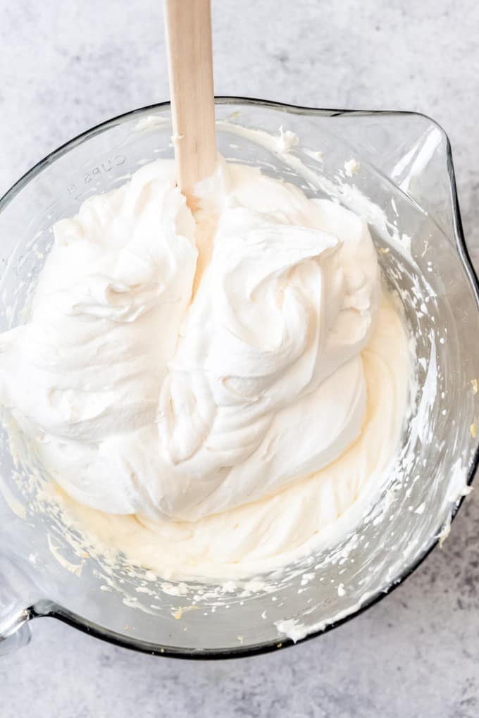 An image of whipped cream being folded into a lemon cream cheese mixture to make the filling for a no-bake dessert.