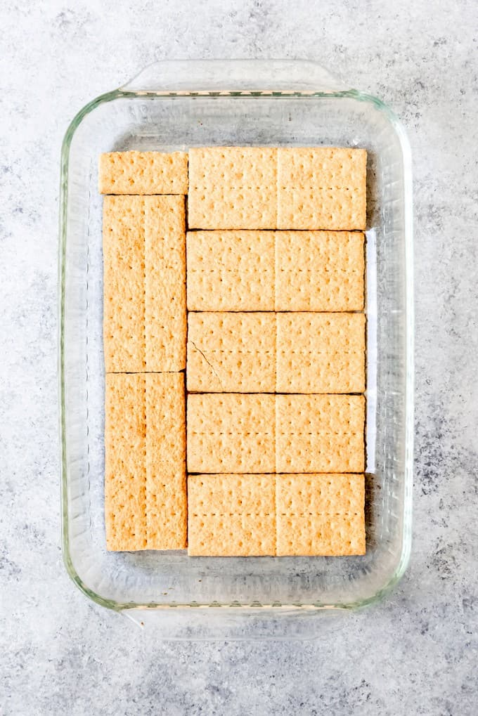 An image of graham cracker squares arranged in the bottom of a 9x13-inch baking dish.