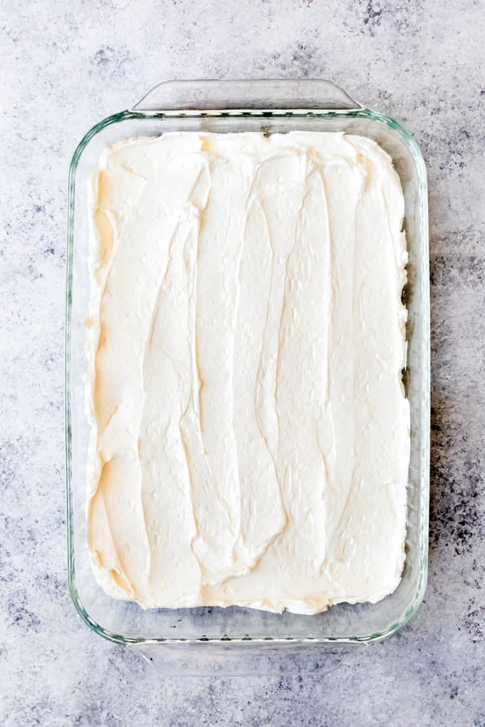 An image of a lemon filling spread in an even layer of graham crackers in a 9x13-inch baking dish.