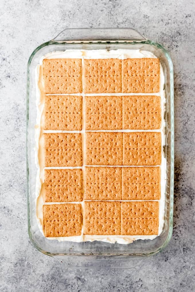 An image of graham cracker squares arranged on top of a creamy lemon layer for a no-bake lemon icebox cake.