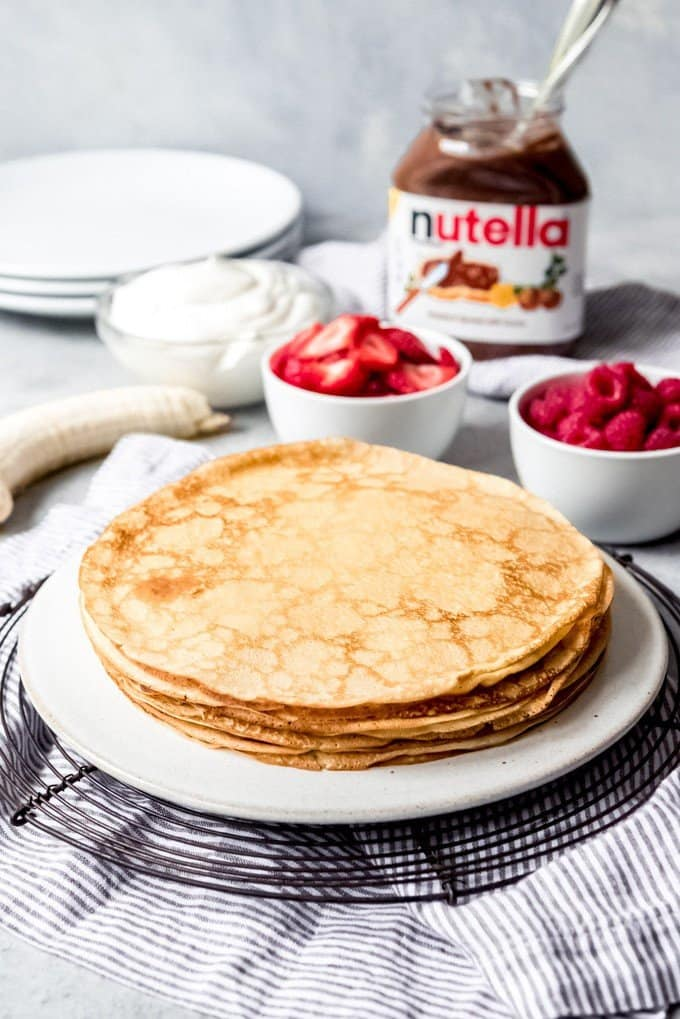 An image of a stack of golden brown crepes with delicate edges made from the best crepes recipe, with fillings like Nutella, strawberries, banana, and whipped cream nearby.