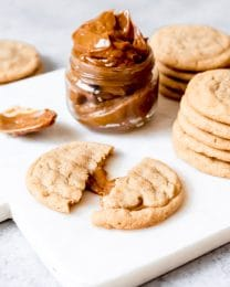 An image of a brown sugar cookie stuffed with dulce de leche with a jar of dulce de leche behind it.