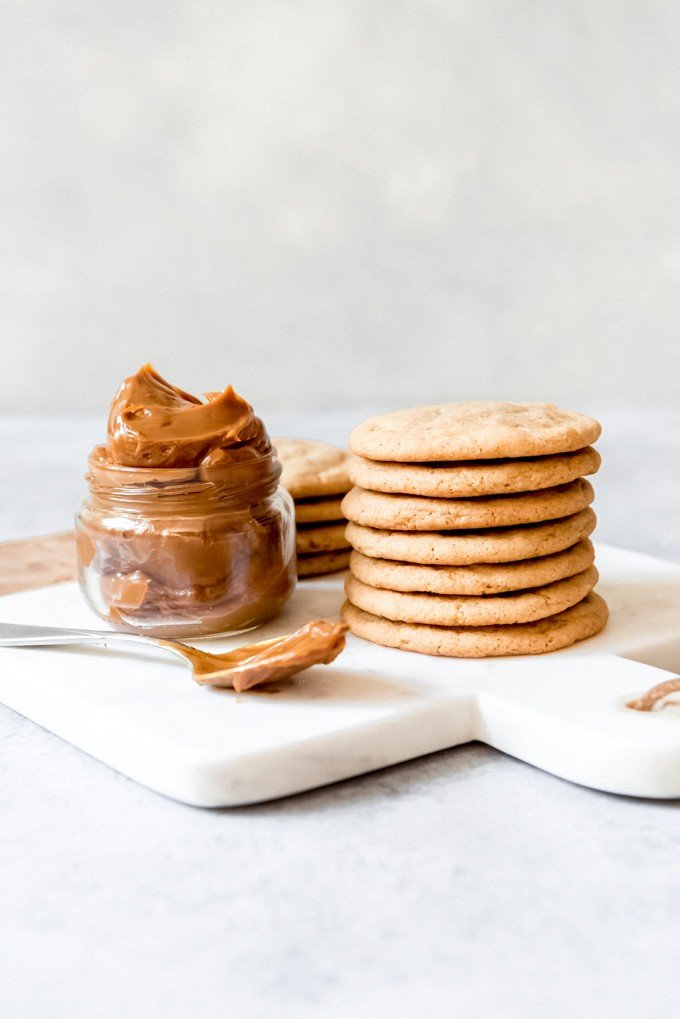 An image of cookies stacked on top of each other next to a jar of dulce de leche.