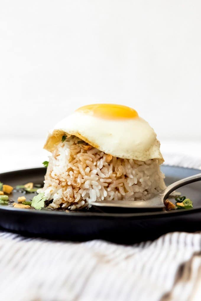 An image of a sunny-side up egg on top of soy glazed sticky rice.