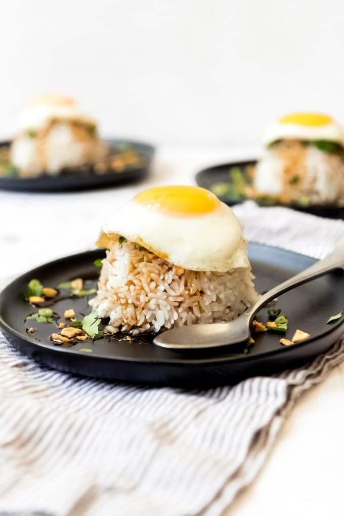 An image of a pile of sticky rice with crispy garlic chips, and a fried egg on top.