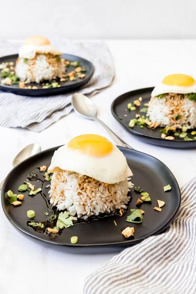 An image of three plates with piles of sticky rice topped with fried eggs.