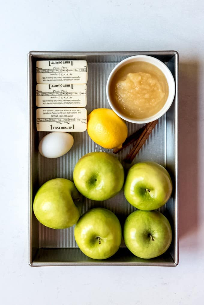 An image of a rectangular cake pan with butter, apples, lemon, egg, applesauce, and cinnamon sticks.