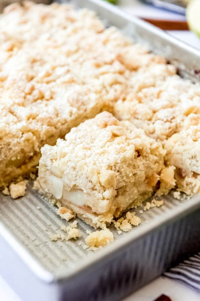 An image of a piece of apple bars with streusel topping.