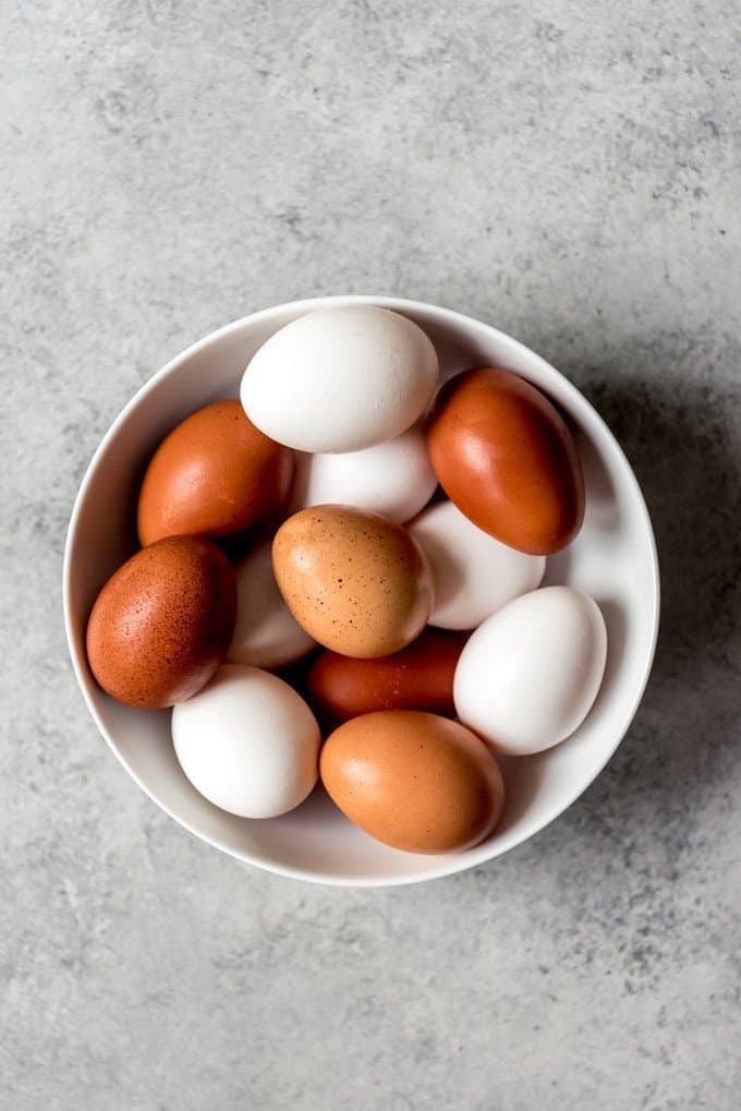 An image of a bowl of both white and brown eggs.