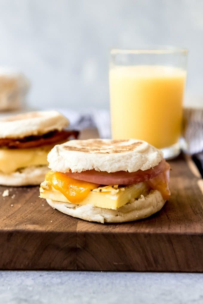 An image of a make-ahead breakfast sandwich with ham, cheddar, and eggs on an English muffin with a glass of orange juice behind it.