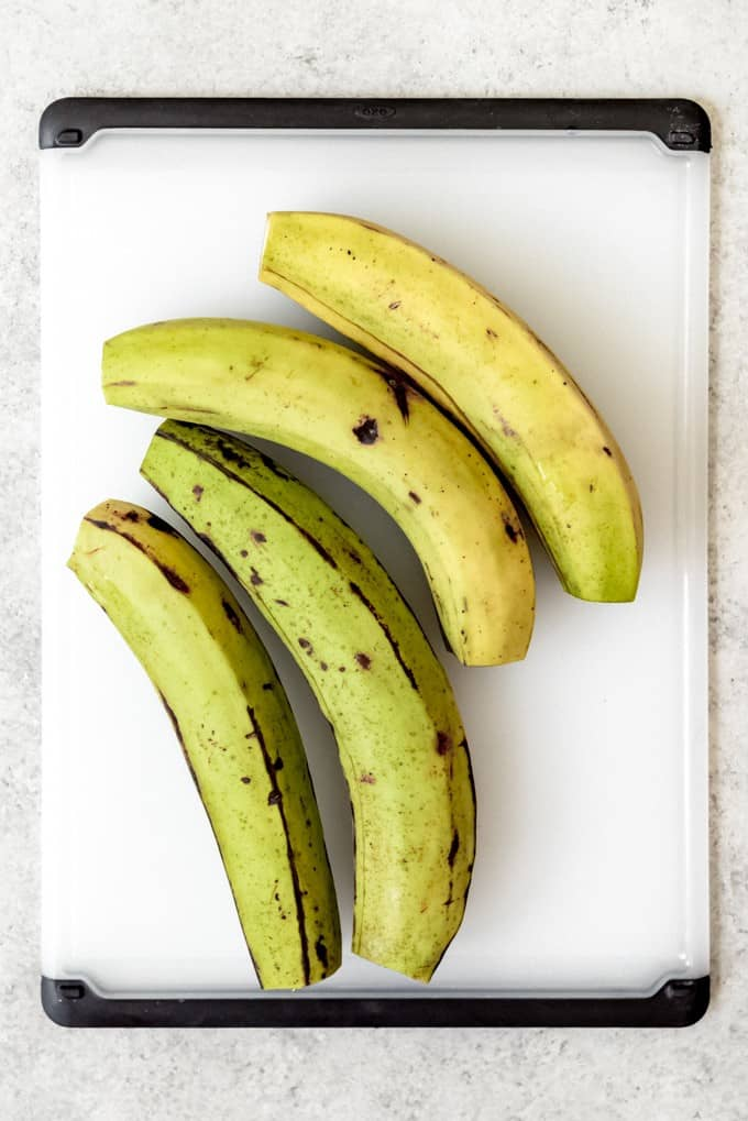 An image of green plantains with their ends sliced off.