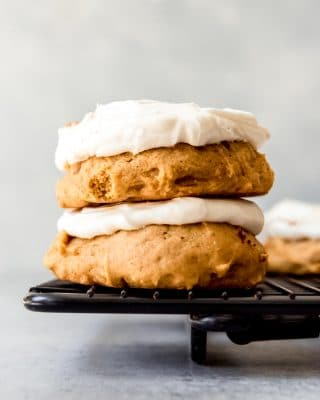An image of pumpkin cookies with cream cheese frosting stacked on top of each other.