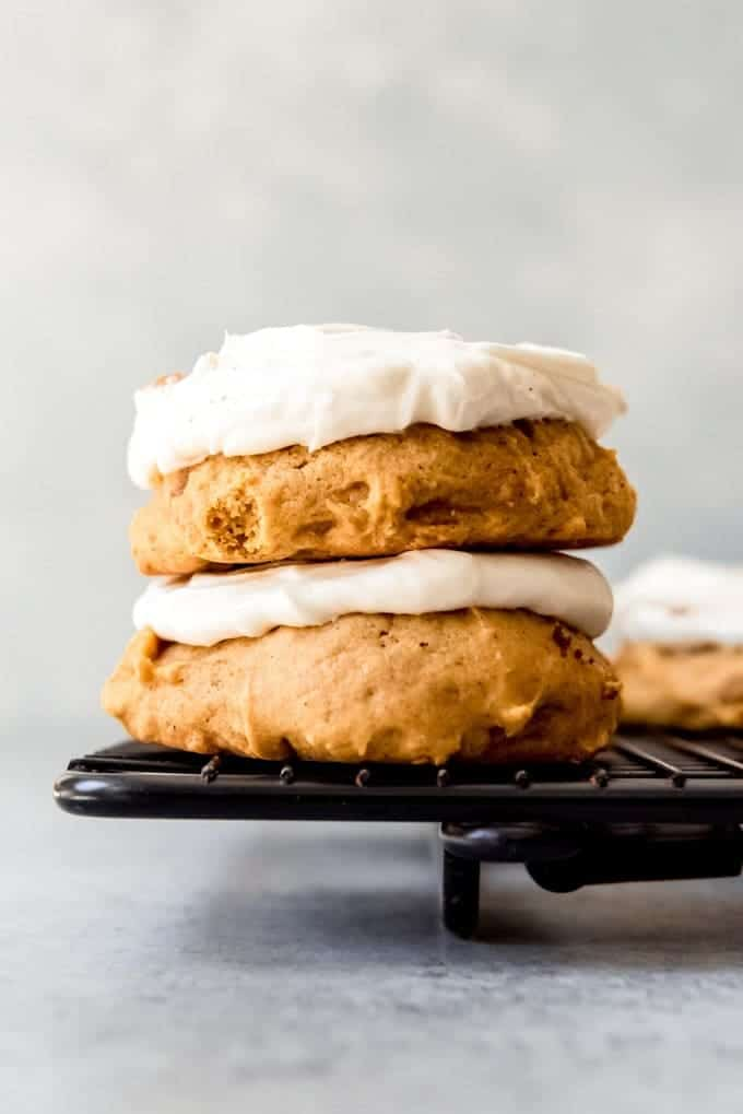An image of two pumpkin cookies with cream cheese frosting stacked on top of each other on a black wire cooling rack.