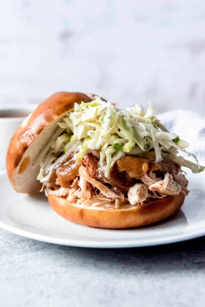 An image of a slow cooker applesauce pulled chicken sandwich with apple cabbage slaw piled on top.