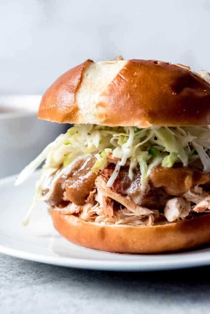 An image of a pulled chicken sandwich on a pretzel bun with apple cabbage slaw.