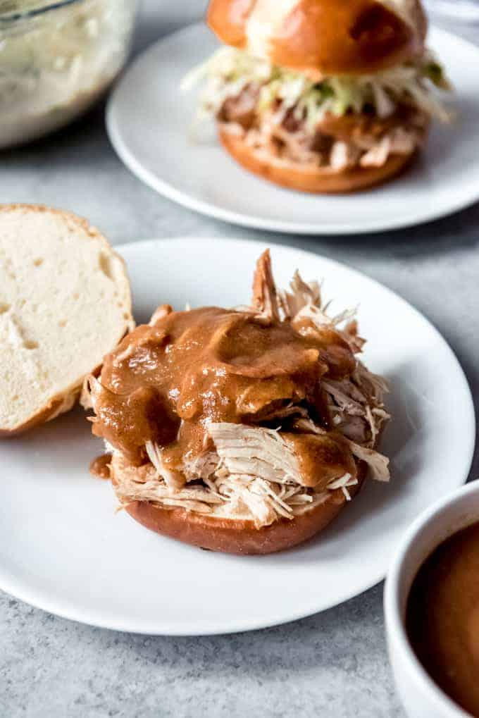 An image of shredded chicken on a bun with an apple barbecue sauce on top.