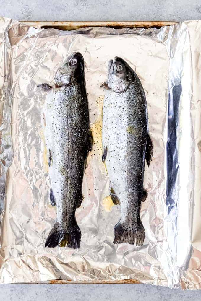 An image of two large rainbow trout on a foil-lined baking sheet.