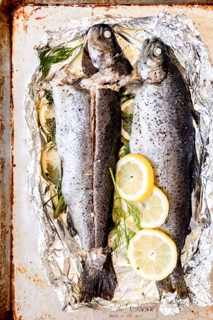 An image of whole baked rainbow trout sliced down the side to remove fillets of fish without the bones.