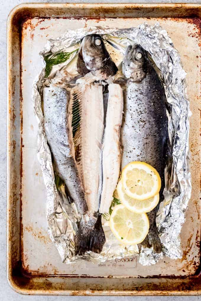 An image of baked rainbow trout on a baking sheet.