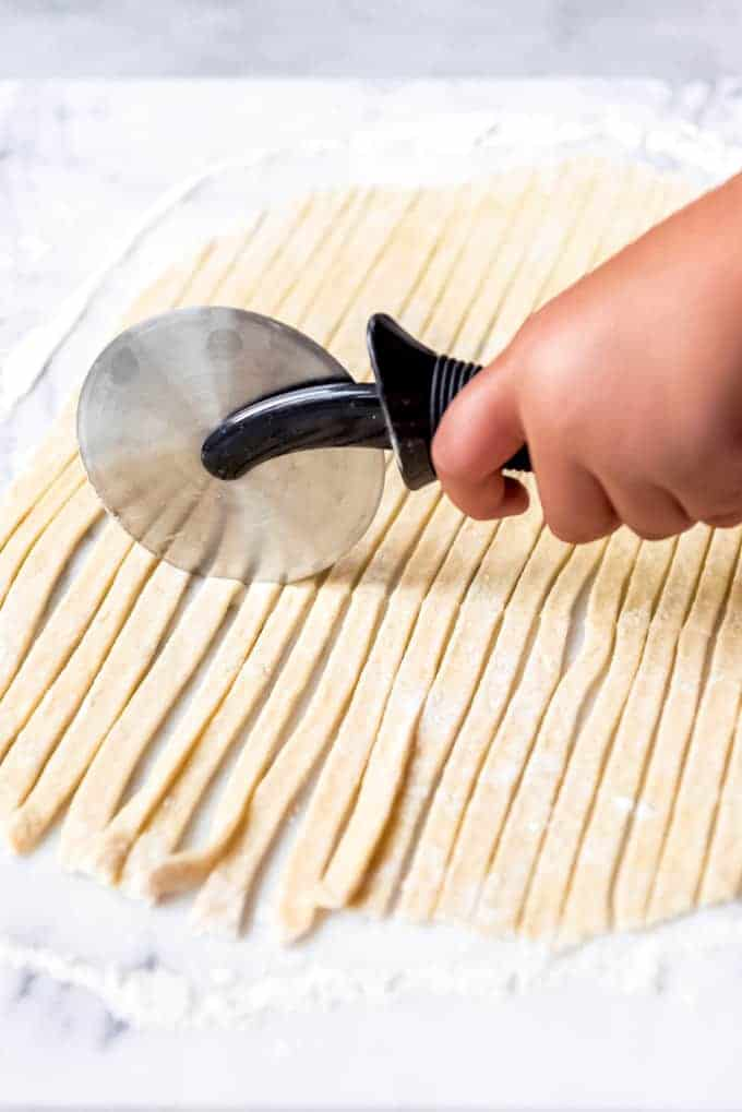 An image of a hand holding a pizza cutter to cut egg noodles into strips.