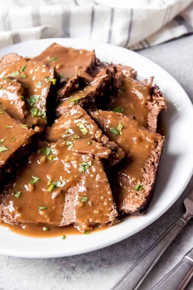 An image of sliced sauerbraten with gravy on a plate.