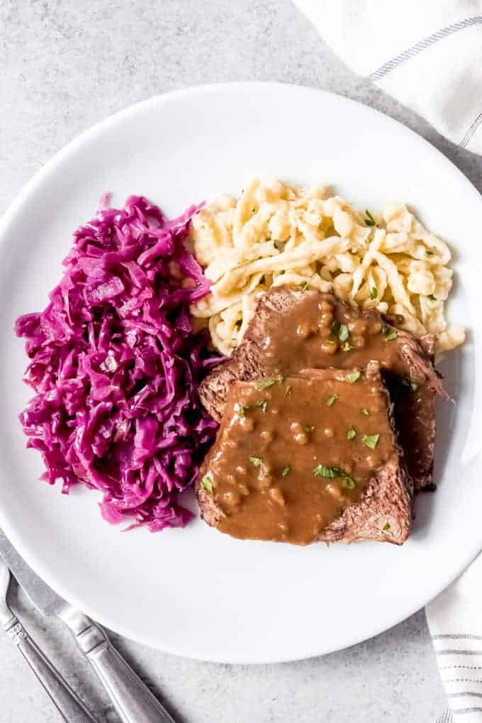 An image of authentic sauerbraten with rotkohl (German red cabbage) and spaetzle on a plate.