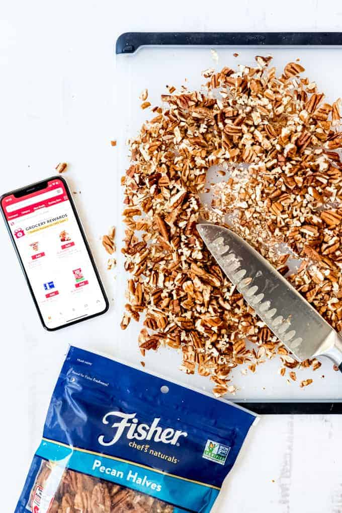 An image of chopped pecans on a cutting board next to a phone with the Safeway app and a bag of Fisher pecan halves.