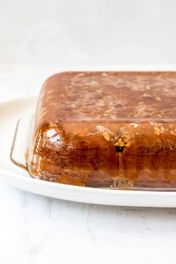 An image of a baking pan turned upside down to release a batch of caramel nut rolls onto a serving plate.