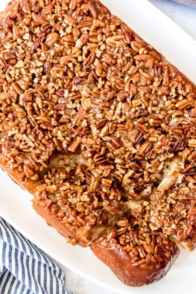 An image of caramel pecan sticky buns that have been turned over onto a serving plate so that the pecans are showing on top.