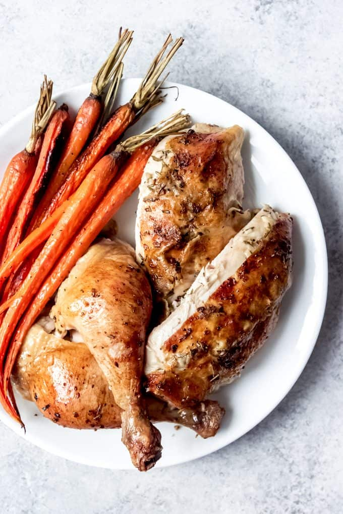 slow roasted chicken cut up with carrots on white plate