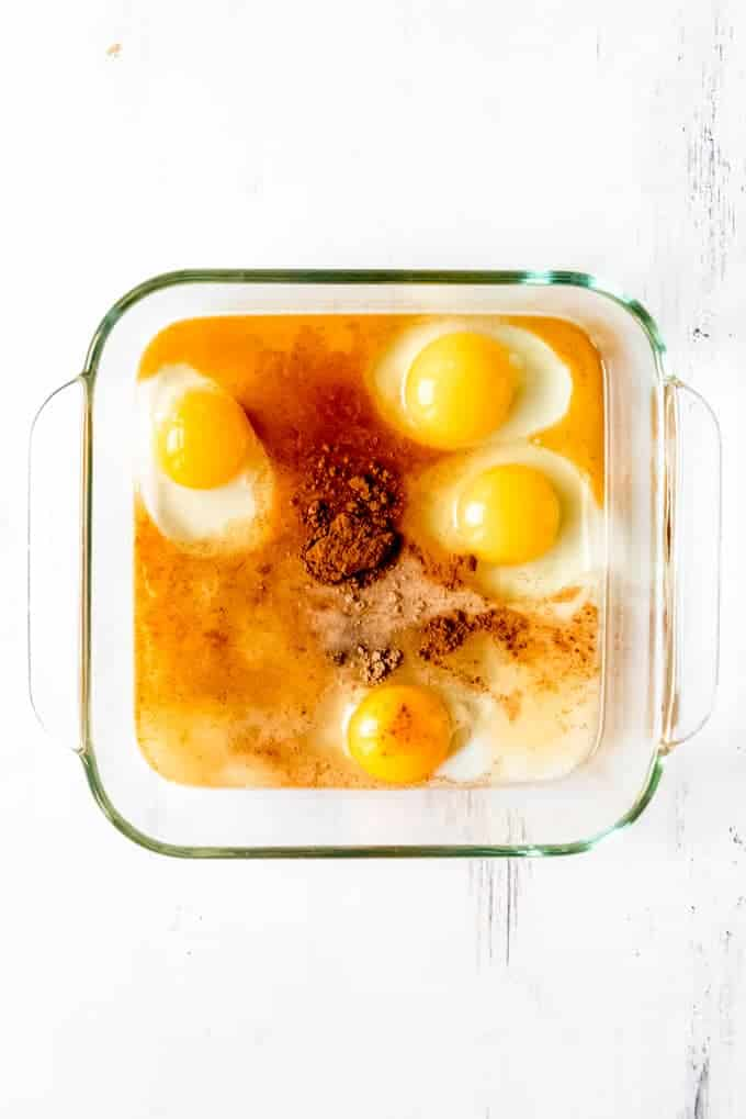 An image of eggs, cinnamon, nutmeg, milk, and brown sugar for making custard for french toast.