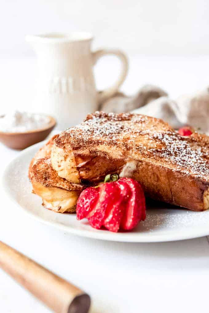 An image of french toast on a plate with a sliced strawberry.