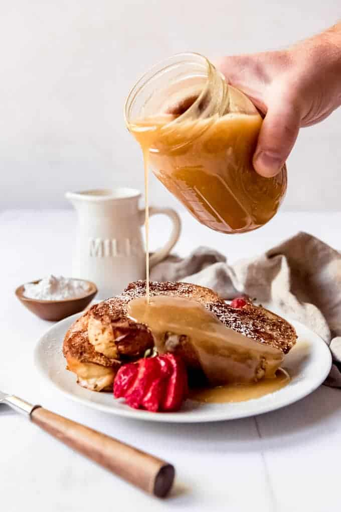 An image of buttermilk caramel syrup being poured over a plate of homemade french toast.